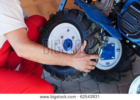 Man Mounting Tyre On A Gasoline Motor  Tiller