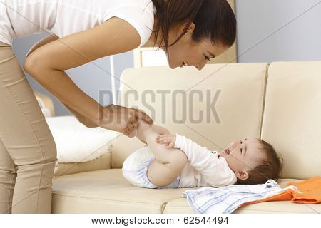 Young mother and baby boy having fun while dressing up on sofa.
