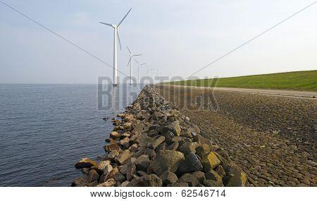 Wind turbines in a lake along a dike