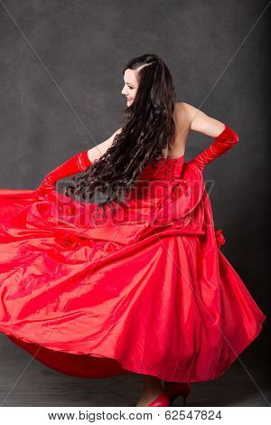 Latino Woman With Long Hair  In Red Waving Dress Dancing  In Action With Flying Fabric On Dark Grey