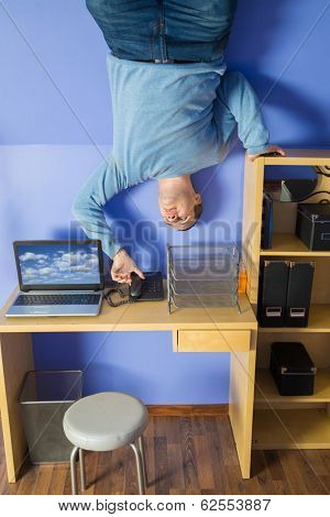 Man in jeans standing on the ceiling under the table with computer