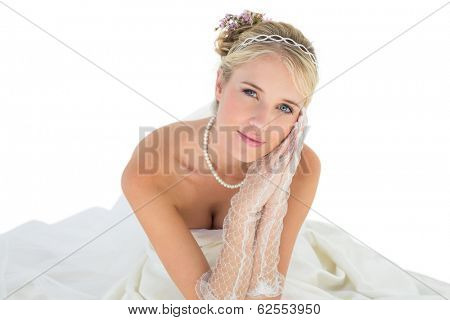 Portrait of bride with hands clasped sitting over white background