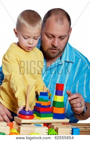 Father and son building blocks on white studio background