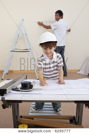 Father And Son Working With Plans At Home