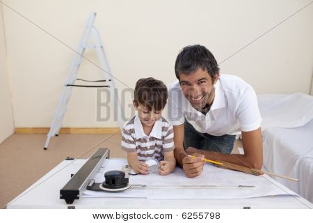 Father And Son Making Architectural Works In Bedroom