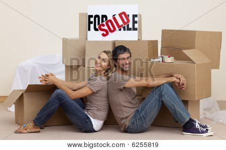 Wife And Husband Relaxing On Floor Unpacking Boxes