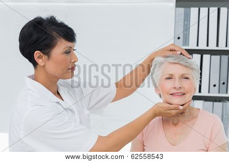 Female chiropractor doing neck adjustment in the medical office
