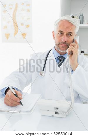 Concentrated male doctor writing reports while on call in the medical office