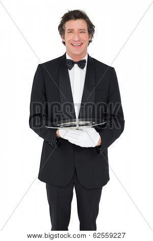 Portrait of happy waiter holding empty tray over white background