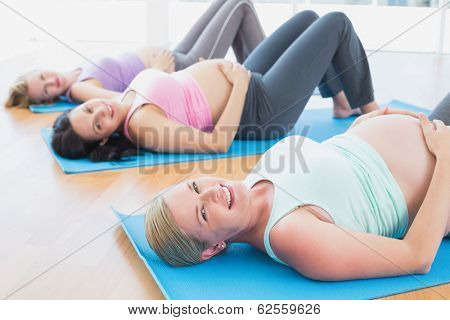Happy pregnant women in yoga class lying on mats in a fitness studio
