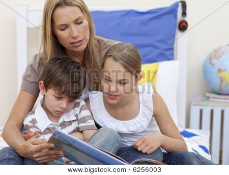 Mother Reading A Book With Her Children In Bed