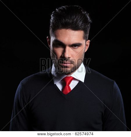 young business man looking into the camera with an angry face. on a black background