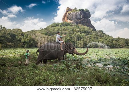 SIGIRIYA, SRI LANKA - 28 FEBRUARY 2014: Man and child riding on the back of elephant with rock of Sigiriya as backdrop and mahout standing at rear.