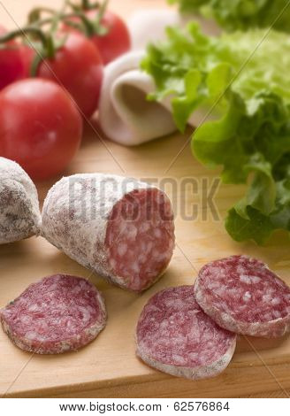 slices of salami with tomatoes and green salad