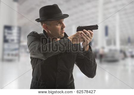 secret service man with gun on grey background