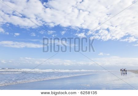 Four young people two couples holding hands looking out to sea on a beach