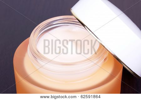 Cream In Orange Box On Black Table