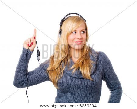 Smiling Young Woman With Headphones Pointing Upwards Over White
