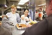stock photo of charity relief work  - Staff Serving Food In Homeless Shelter Kitchen - JPG