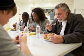 stock photo of charity relief work  - People Sitting At Table Eating Food In Homeless Shelter - JPG