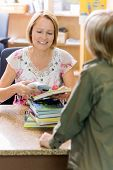 stock photo of librarian  - Mature female librarian scanning books at counter while boy standing in library - JPG