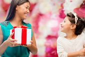 holidays, presents, family, child, christmas and x-mas concept - happy mother and child girl with gi
