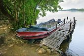 picture of dock a pond  - motorboat at the dock on the river bank - JPG