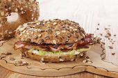stock photo of bagel  - Whole grain bagel with bacon on wooden kitchen board on wooden background - JPG