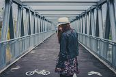 picture of girl walking away  - Pretty girl with long hair walking away on a bridge - JPG