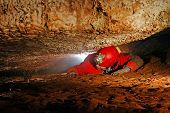 stock photo of cave woman  - Narrow cave passage with a spelunker explorer