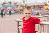 Boy in the amusement park on a background of carousels.