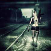 stock photo of doomsday  - Sexy blond woman killer holding automatic and gun - JPG