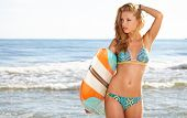 Beautiful Young Woman Surfer Girl in Bikini with Surfboard at a Beach