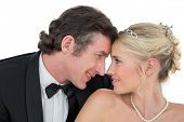 Smiling bride and groom with head to head against white background