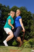 stock photo of skipping rope  - Mother and daughter skipping a rope in the garden - JPG