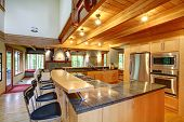 foto of stool  - View of kitchen back with black high stools steel appliances and ceiling beams - JPG