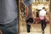 stock photo of terrorist  - Man Holding Gun against an hotel background - JPG
