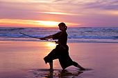 Young samurai women with Japanese sword(Katana) at sunset on the beach