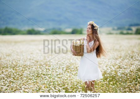 Young woman in a field of daisies