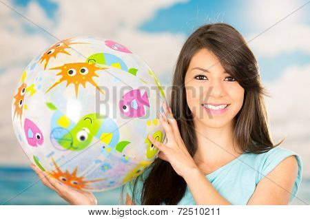beautiful young girl playing with beach ball