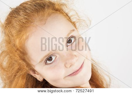Closeup Natural Portrait Of Little Red-haired Girl Looking Straight To The Camera