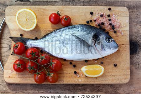 Two Fresh Gilt-head Bream Fish On Cutting Board