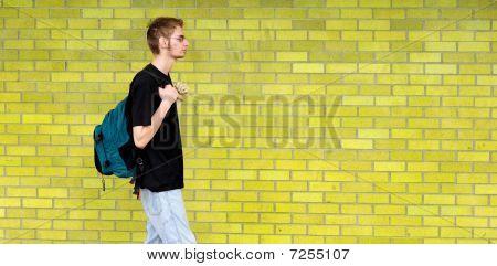 Estudante, caminhando para além da parede de tijolo