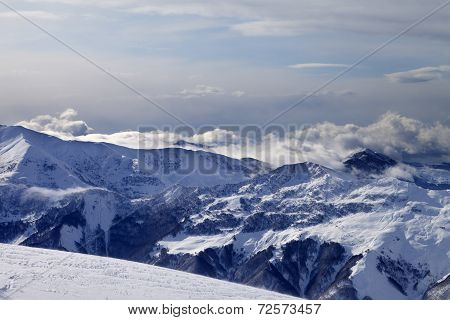 Winter Mountains In Clouds And Ski Slope
