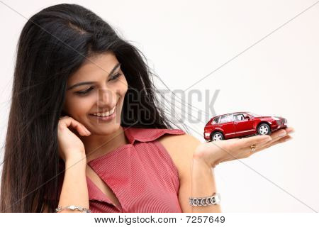 Smiling girl holding toy car