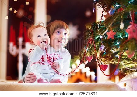 Happy Laughing Children Playing Under A Beautiful Christmas Tree