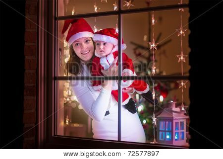 Young Mother And Baby Dressed As Santa