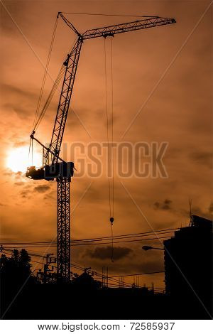 Silhouetted Construction Crane Operated During The Sunset In The Evening