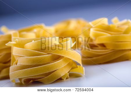 Tagliatelle pasta on white blue background.Macro concept