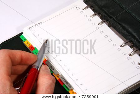 A Hand Writing In A blank Organizer With A Red Pen